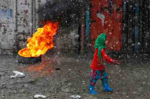 An Afghan woman walks past a burning tyre along a street on a snowy day in Kabul